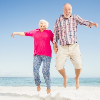 Happy senior couple jumping on the beach