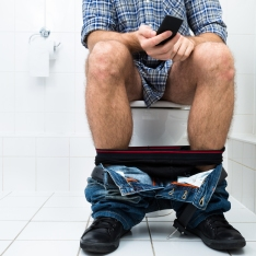 Man In Toilet Using Cellphone