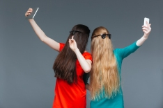 Two funny young women covered face with long hair and taking sel