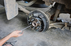 A mechanic changing the brake shoe on a car.