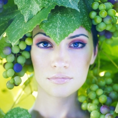 Grape goddess. Beautiful young lady wrapped in grape